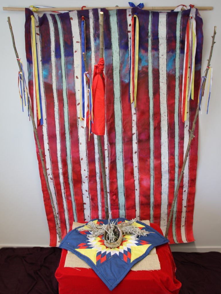 "Prayers for My Sisters, ""This series is about recognizing that within the issue of MMIWG; the women are cared for spiritually. They are prayed for and ceremonies held for them. The red background pays homage to the work done like ""The Red Dress"" by Jaime Black which has raised awareness since 2011. The 12 sticks represent the lodges and the ribbons represent the prayers. I have supplied an image of a painting and also the Installation which allows people to interact with the piece."" Dawn Marie Marchand."